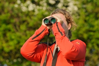 Young woman birdwatching at Rutland Water